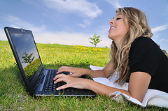 Young lady working outside on her laptop